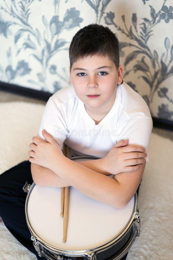 Garçon d'adolescent avec un tambour dans la chambre image stock