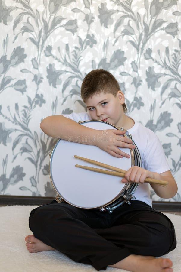 Garçon d'adolescent avec un tambour dans la chambre images libres de droits