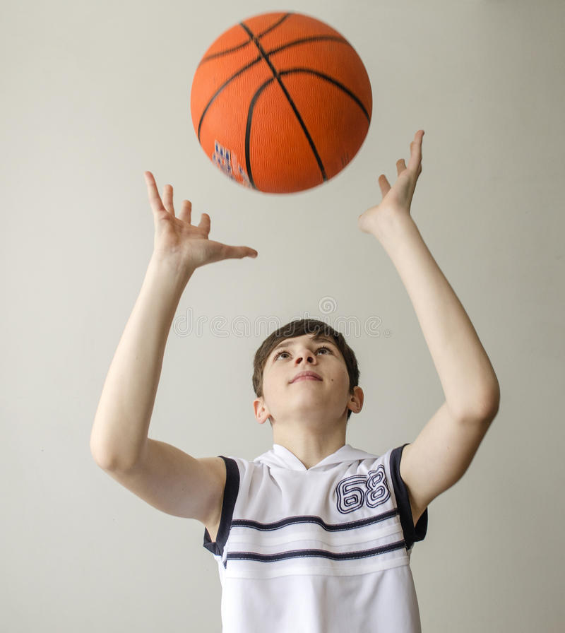 Garçon d'adolescent dans une chemise blanche avec une boule pour le basket-ball image libre de droits