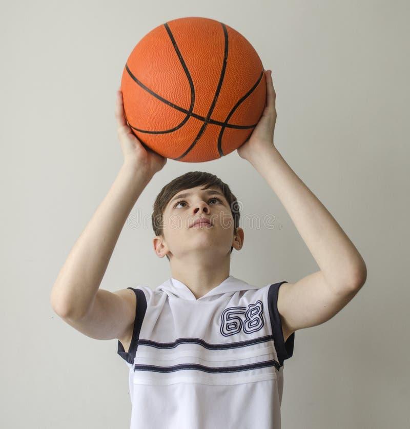 Garçon d'adolescent dans une chemise blanche avec une boule pour le basket-ball image stock