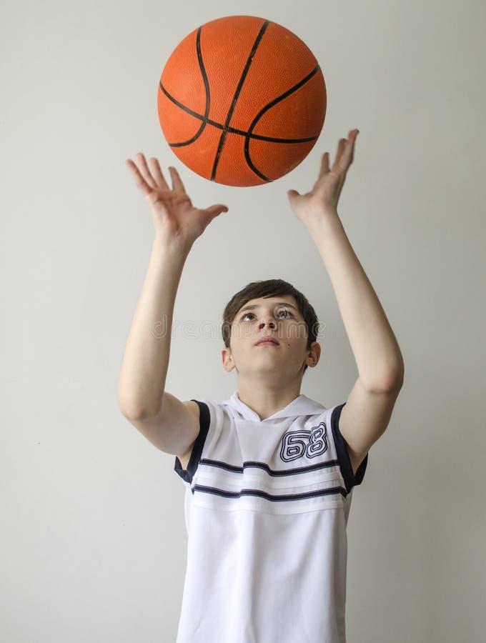 Garçon d'adolescent dans une chemise blanche avec une boule pour le basket-ball photographie stock libre de droits