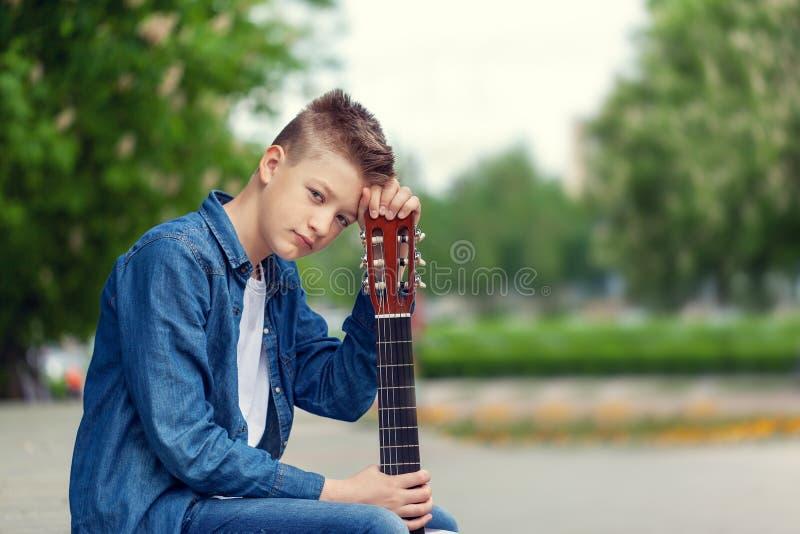 Garçon d'adolescent de portrait avec la guitare se reposant en parc images libres de droits