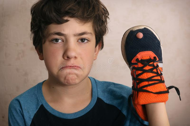 Garçon d'adolescent frustré au sujet du trou dans des ses chaussures préférées d'entraîneurs photos stock