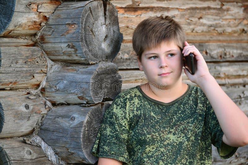 Garçon d'adolescent parlant au téléphone portable se tenant prêt image libre de droits