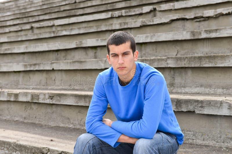Garçon d'adolescent s'asseyant sur des escaliers et regardant l'appareil-photo images libres de droits