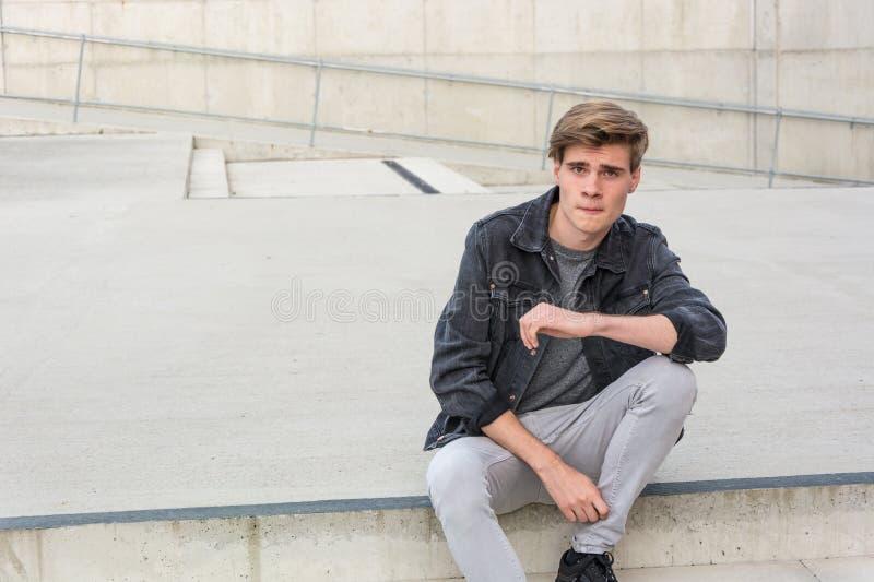 Garçon d'adolescent s'asseyant sur des escaliers réfléchis au sujet des choix photos libres de droits