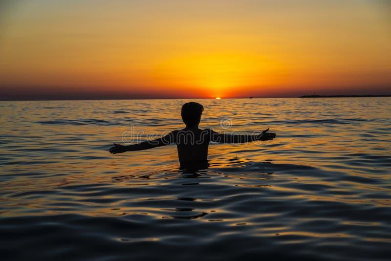 Garçon d'adolescent se baignant sur une plage au coucher du soleil en Sicile photographie stock libre de droits