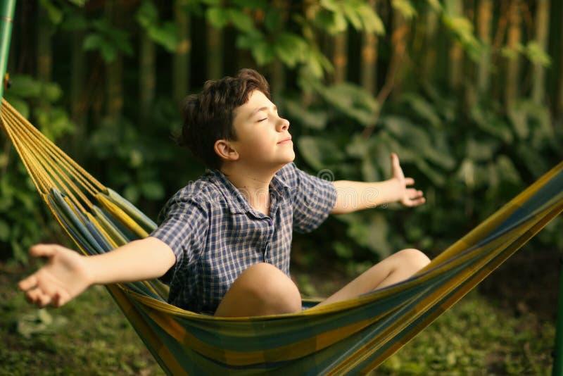 Garçon d'adolescent se reposant dans l'hamac photographie stock