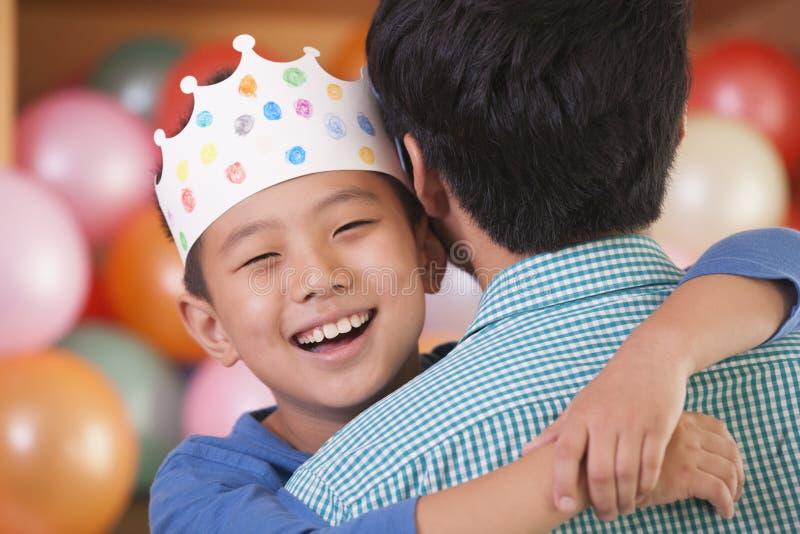 Garçon d'anniversaire étreignant son père image libre de droits
