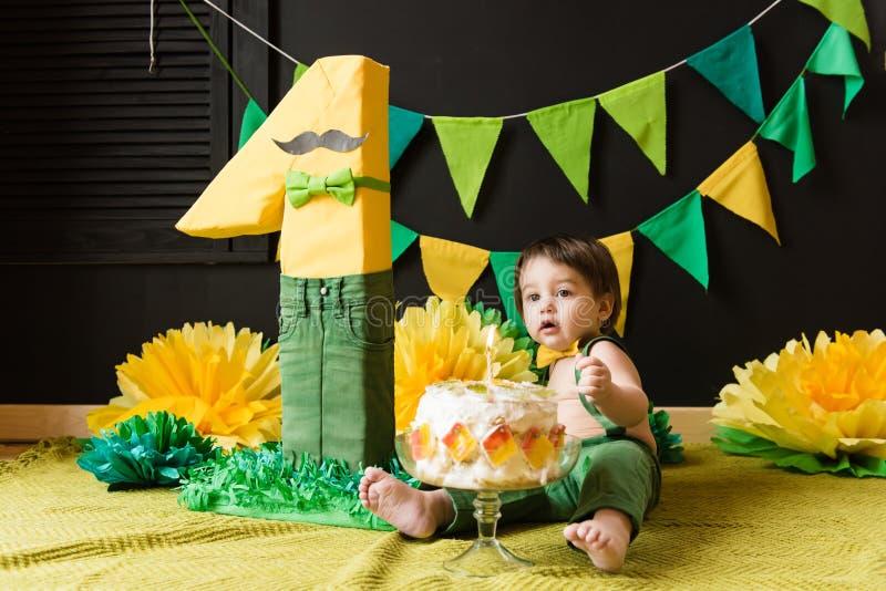 Garçon d'anniversaire avec le schéma un et gâteau avec la bougie image stock