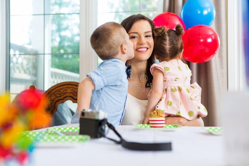 Garçon d'anniversaire embrassant la mère à la maison photographie stock libre de droits