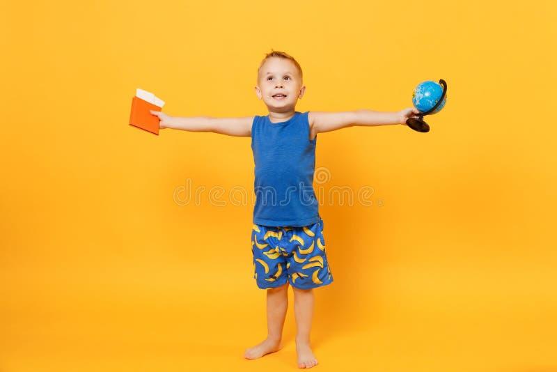 Garçon d'enfant 3-4 années dans le passeport bleu de globe de prise de vêtements d'été de plage d'isolement sur le fond jaune-ora photos libres de droits