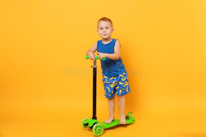Garçon d'enfant 3-4 années portant les vêtements bleus d'été de plage sur le scooter d'isolement sur le fond jaune-orange lumineu photographie stock libre de droits