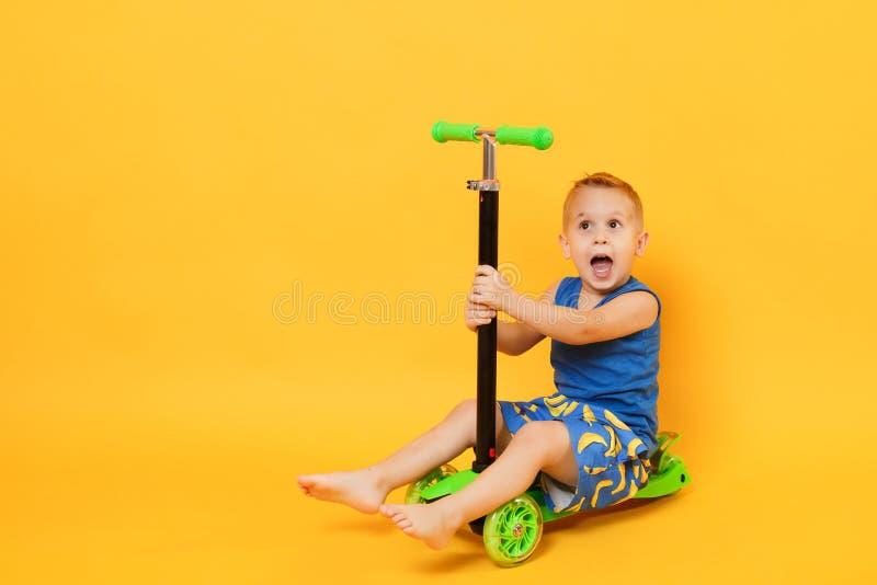 Garçon d'enfant 3-4 années portant les vêtements bleus d'été de plage sur le scooter d'isolement sur le fond jaune-orange lumineu photos libres de droits