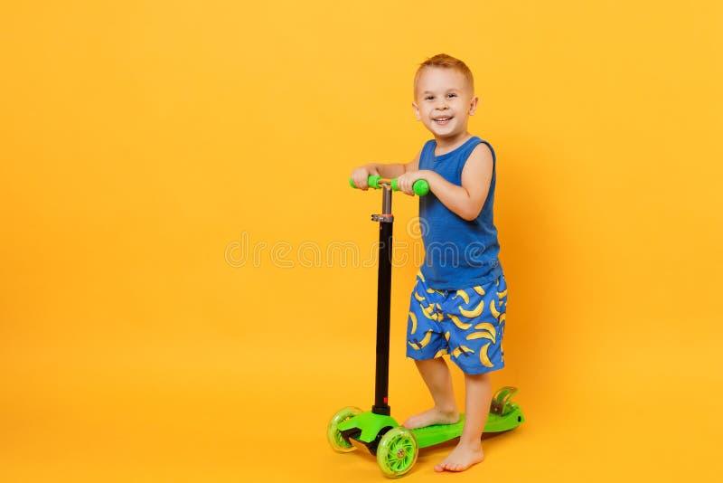 Garçon d'enfant 3-4 années portant les vêtements bleus d'été de plage sur le scooter d'isolement sur le fond jaune-orange lumineu image libre de droits