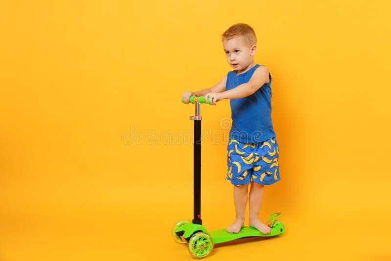 Garçon d'enfant 3-4 années portant les vêtements bleus d'été de plage sur le scooter d'isolement sur le fond jaune-orange lumineu photo libre de droits
