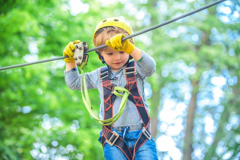 Garçon d'enfant ayant l'amusement au parc d'aventure Enfant heureux s'?levant dans les arbres Petit enfant heureux grimpant à un  photo libre de droits