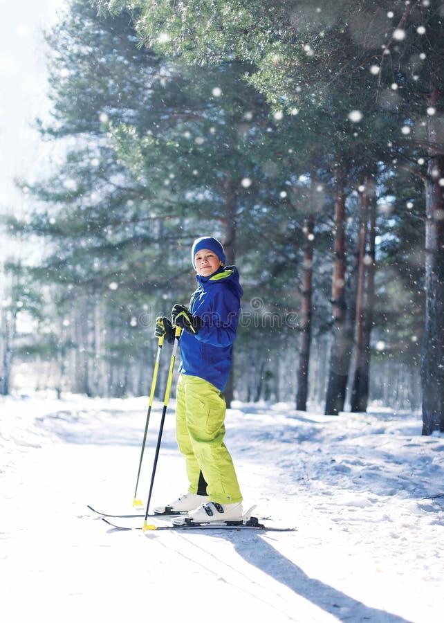 Garçon d'enfant de skieur dans les vêtements de sport avec le ski au-dessus de l'hiver photos stock