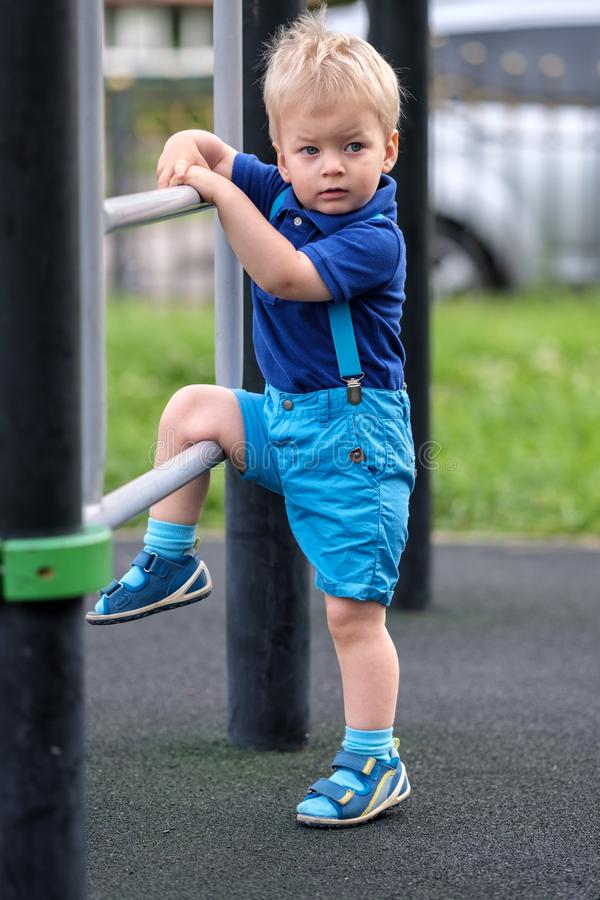 Garçon d'enfant en bas âge aux shorts de port et aux bretelles de terrain de jeu photo stock