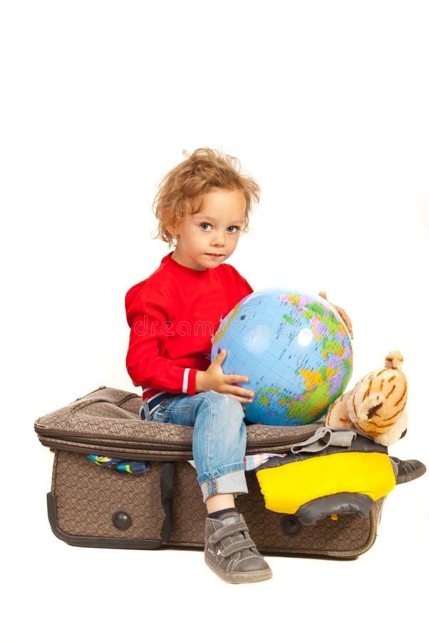Garçon d'enfant en bas âge avec le globe se reposant sur le bagage photographie stock