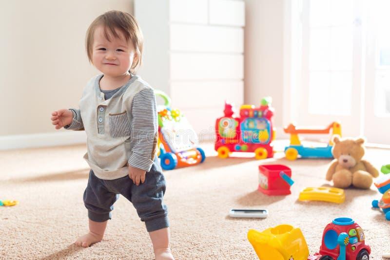 Garçon d'enfant en bas âge dans sa salle de jeux avec des jouets photographie stock