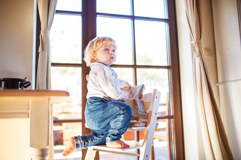 Garçon d'enfant en bas âge dans un dangereux à la maison, s'élevant dans le highchair images stock