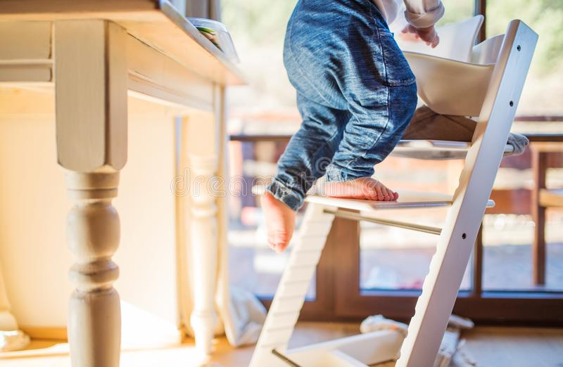 Garçon d'enfant en bas âge dans un dangereux à la maison, s'élevant dans le highchair photo stock