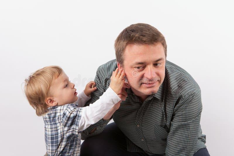 Garçon d'enfant en bas âge inspectant sa prothèse auditive du ` s de père dans son oreille photos libres de droits