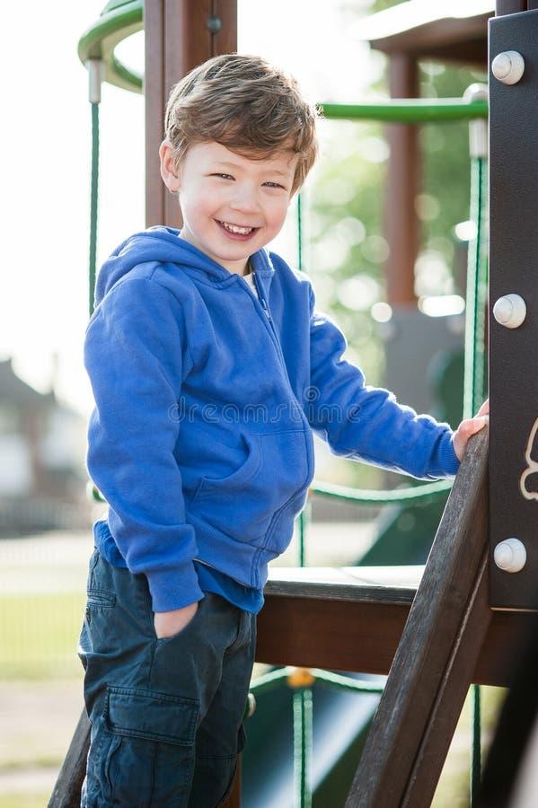 Garçon d'enfant en bas âge souriant sur un cadre de s'élever photo libre de droits