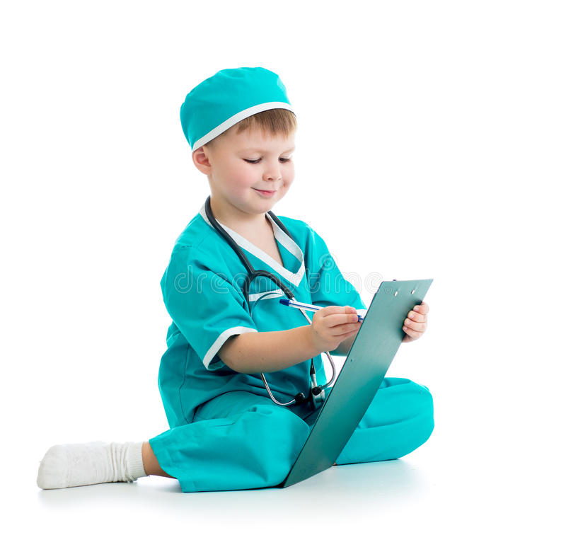 Enfant en uniforme comme docteur écrivant au presse-papiers d'isolement dessus images stock