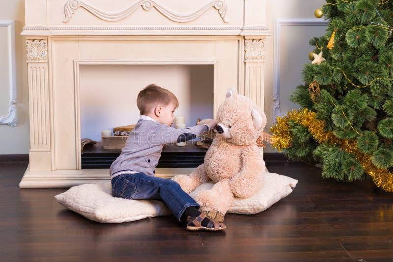 Garçon d'enfant jouant avec l'ours mol de jouet sous l'arbre de Noël photos libres de droits