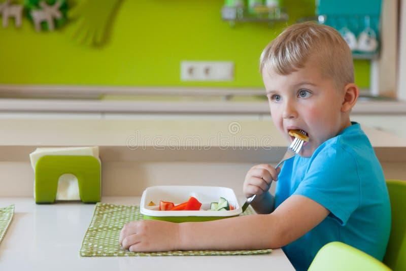 Garçon d'enfant mangeant de la salade de légume frais photos stock