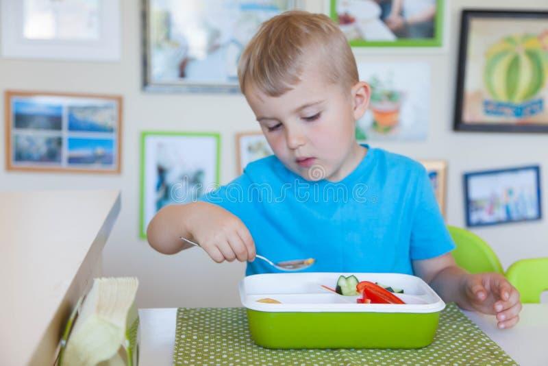 Garçon d'enfant mangeant de la salade de légume frais photo libre de droits