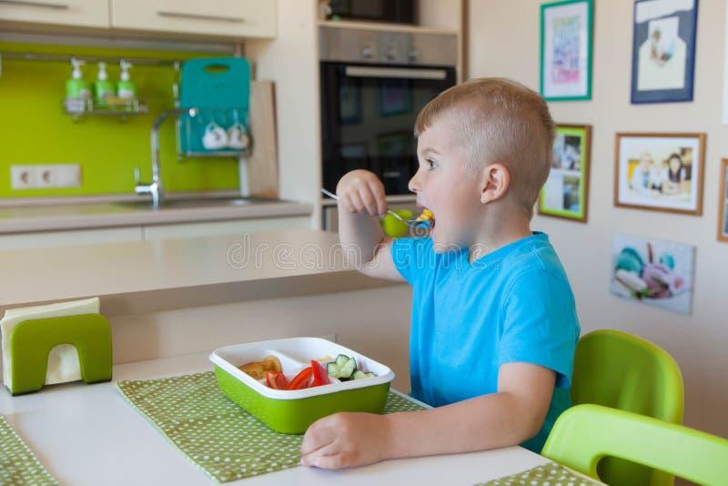 Garçon d'enfant mangeant de la salade de légume frais image stock