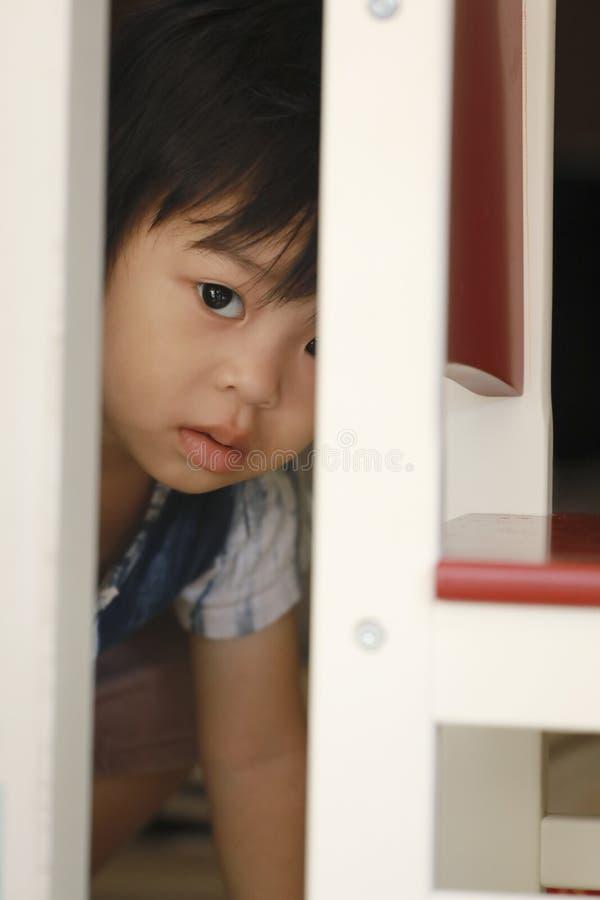 Garçon d'enfant recherchant quelque chose par la porte images stock
