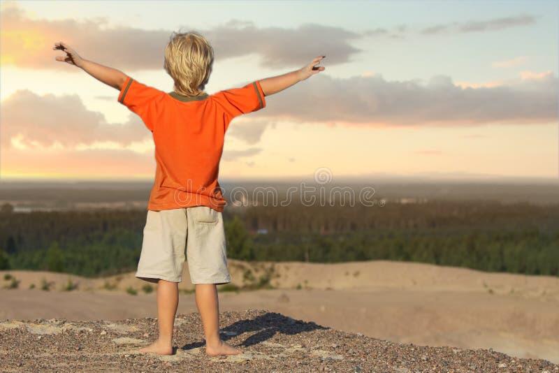 Garçon d'enfant regardant le lever de soleil sur la montagne de sable photos libres de droits