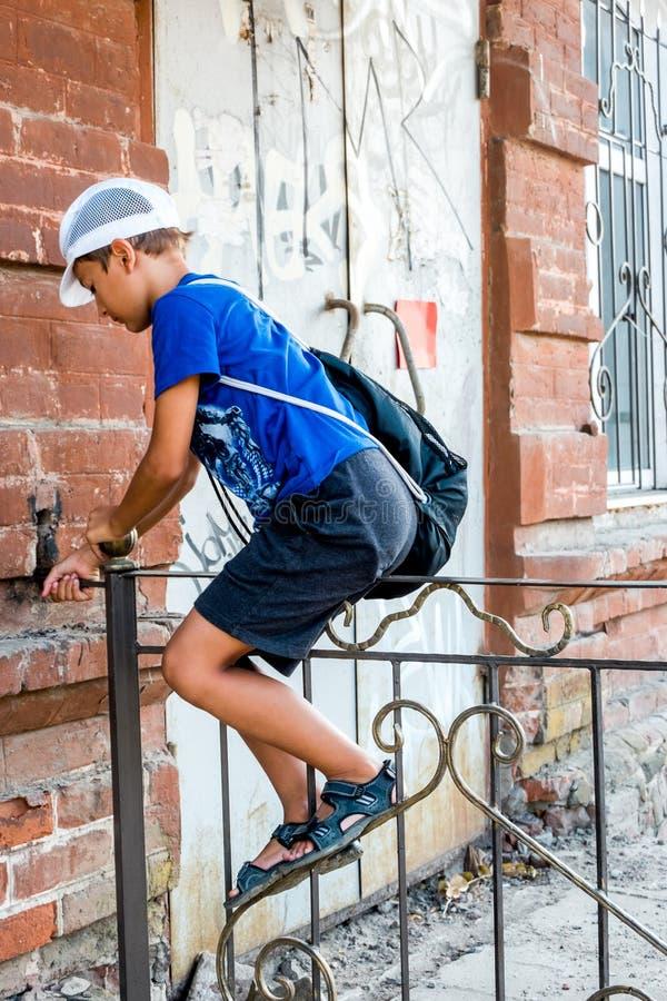 Garçon d'enfant s'élevant au-dessus de la barrière en métal dans une rue, photographie stock