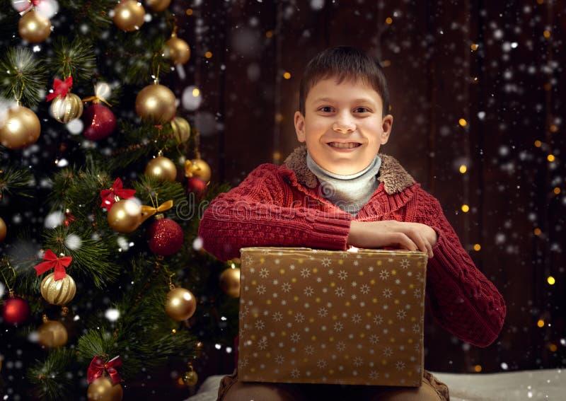 Garçon d'enfant s'asseyant avec le boîte-cadeau près de l'arbre de sapin décoré par Noël, fond en bois foncé photo libre de droits
