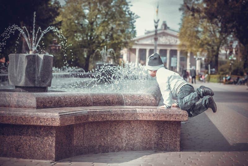 Garçon d'enfant sautant et regardant sur la fontaine photographie stock