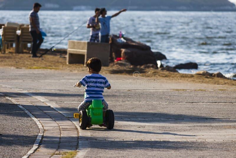 Garçon d'enfant seul montant au bord de la mer photographie stock