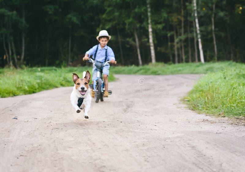 Garçon d'enfant sur l'équitation de bicyclette après le chien fonctionnant par le chemin de terre de pays photographie stock libre de droits