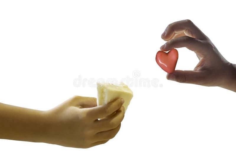 Garçon d'isolement de main tenant le sandwich à pain et tenant un coeur rouge de forme de sucrerie sur un fond blanc images stock