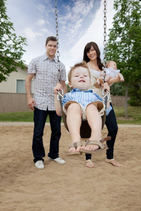 Garçon d'And Mother Pushing de père sur l'oscillation images stock