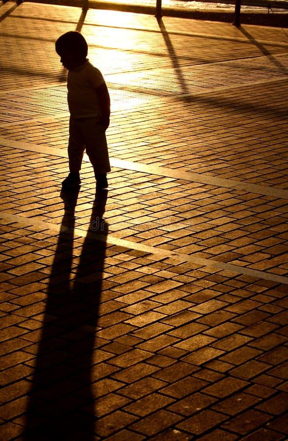 Garçon d'ombre de coucher du soleil photos stock