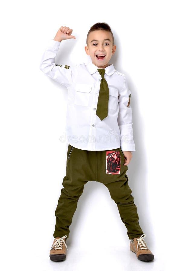 Garçon dans des jeans militaires de vert de T-shirt tenant et donnant des pouces photos libres de droits