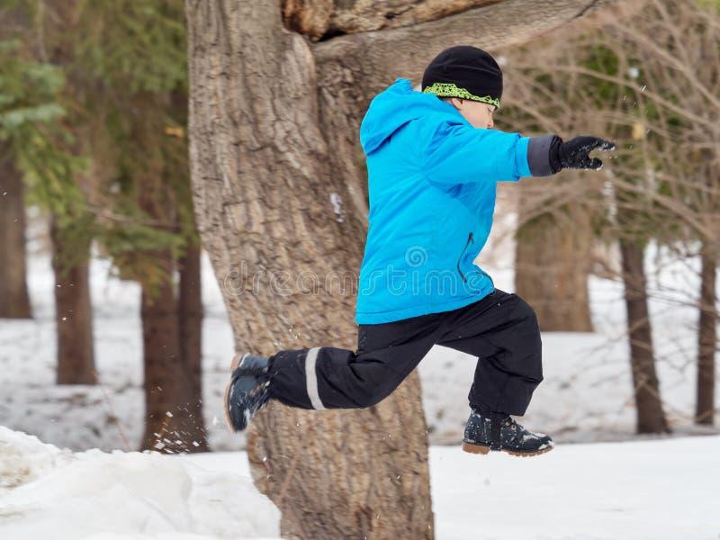 Garçon dans des sauts de parc d'hiver dans la congère photo stock