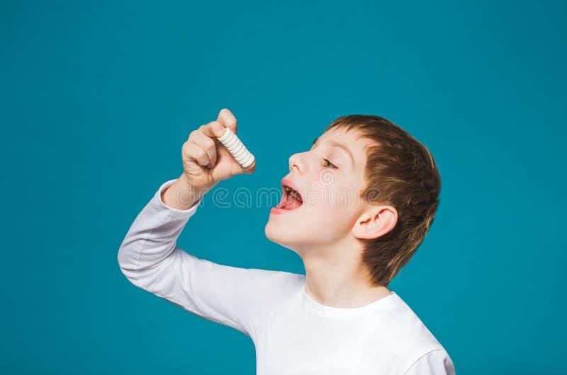 Garçon dans des vêtements blancs mangeant beaucoup de pilules photo libre de droits
