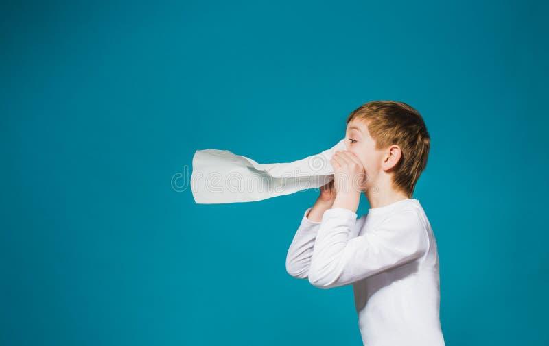 Garçon dans des vêtements blancs soufflant son nez image libre de droits
