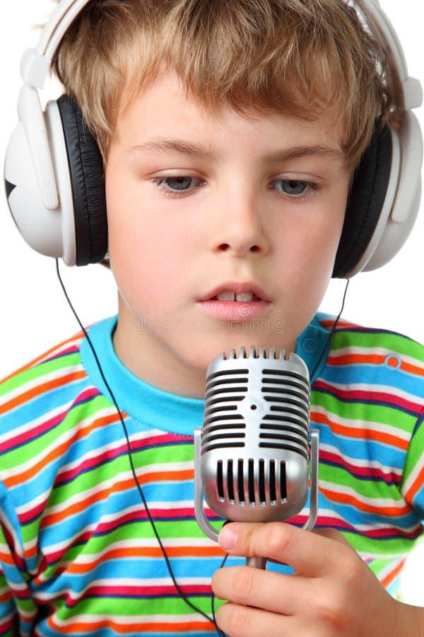 Garçon dans l'écouteur avec le microphone dans des mains ouvertes photos libres de droits