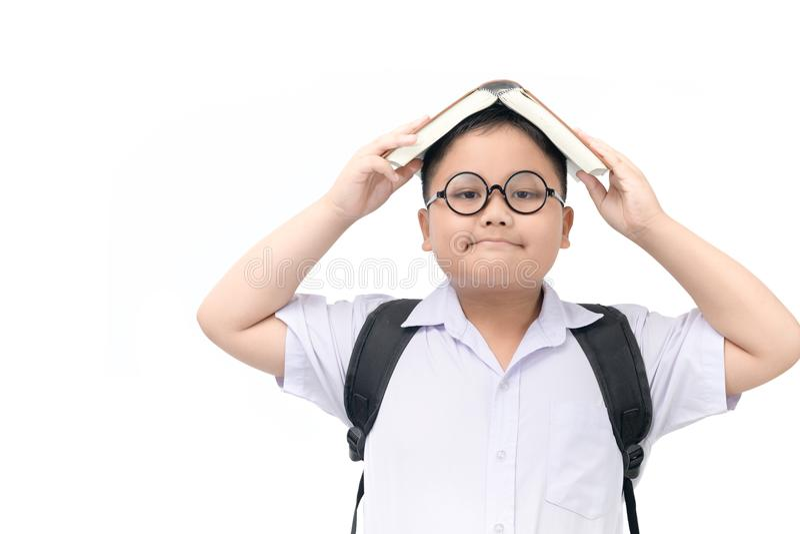 Garçon dans l'étudiant uniforme avec le livre sur la tête images libres de droits